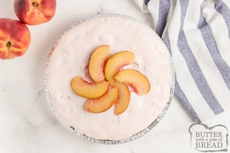 Creamy Peach Pie is made with only 5 ingredients in only a few minutes! Peach Jell-O, vanilla ice cream and fresh peaches are combined into a delicious, no-bake pie recipe!