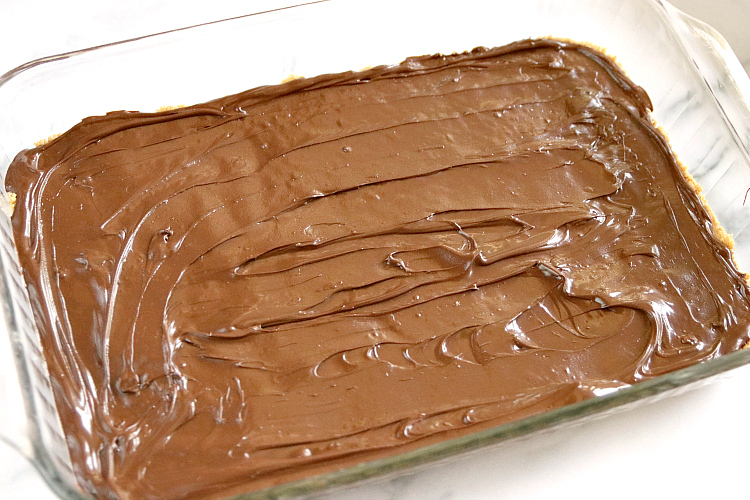 Spreading melted chocolate on the no bake peanut butter bars