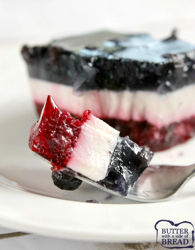 Patriotic Layered Jello Salad has a raspberry layer and a blueberry layer with a delicious vanilla layer in between! This red, white and blue dessert is perfect for the 4th of July and is so yummy, you'll want to eat it the rest of the year too!