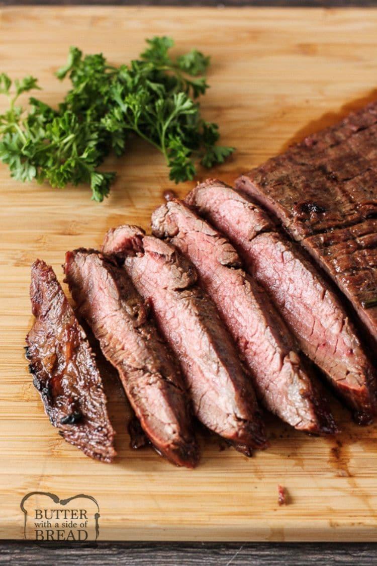 sliced flank steak on a wooden cutting board