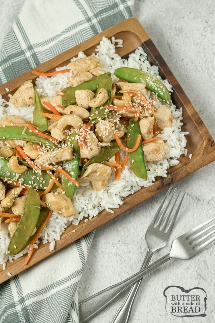 cashew chicken over rice on a wooden platter