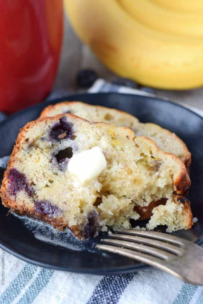 Banana Blueberry cream cheese bread on a black plate with a piec cut out