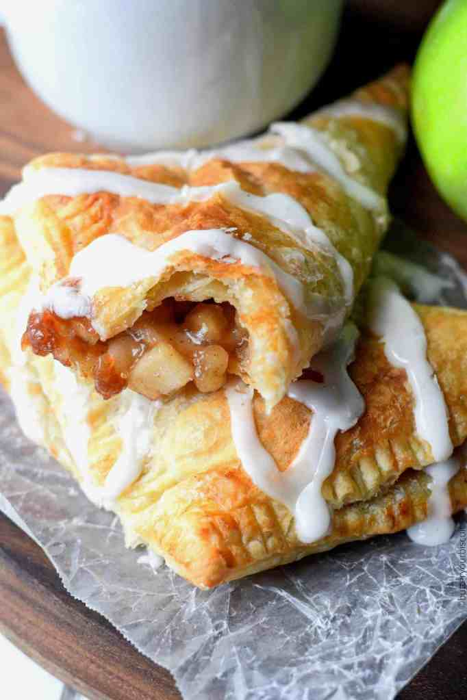 apple turnovers with glaze drizzle over top and a white coffee cup and green apple