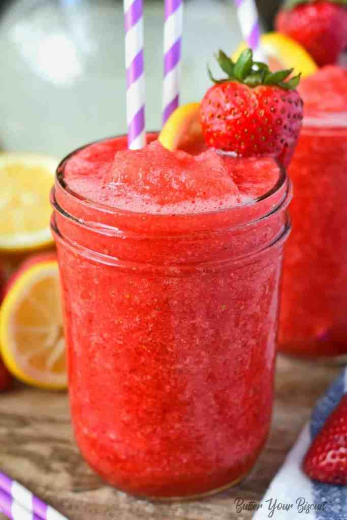 strawberry lemonade vodka slush in a glass with a strawberry and lemon slice