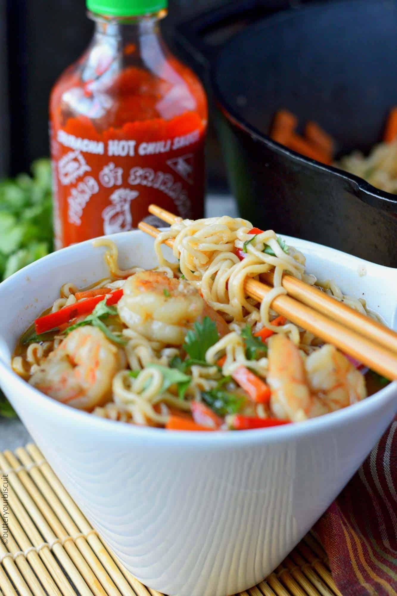 Spicy shrimp ramen bowl with sriracha bottle