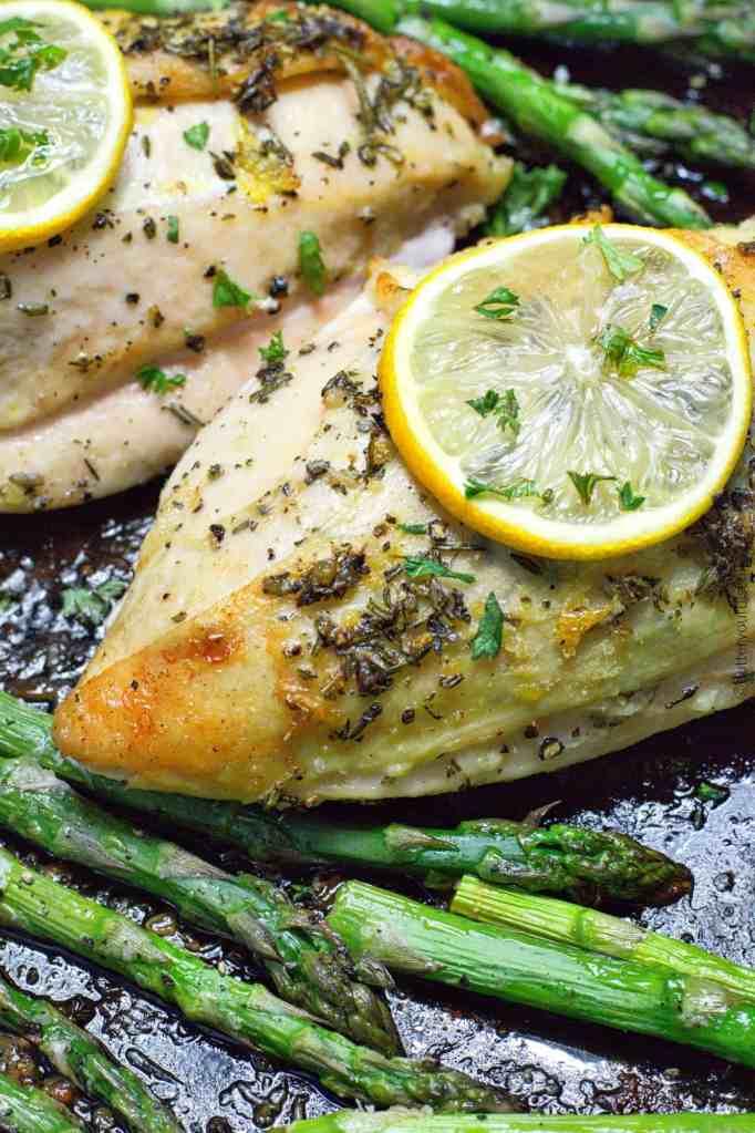 sheet pan lemon herb chicken on a baking sheet with asparagus