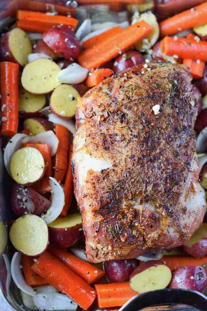 Garlic rosemary roasted pork shoulder in roasting pan
