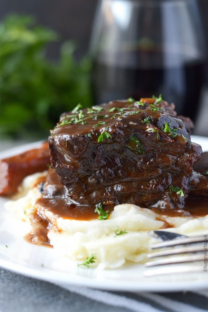 Beef short ribs braised in red wine on a plate with carrots and mashed potatoes