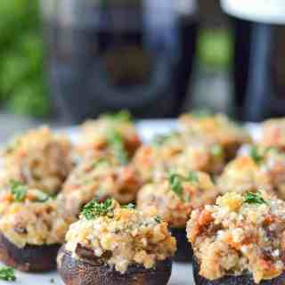 italian sausage stuffed mushrooms on a serving plate with wine