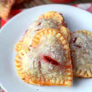Heart shaped cherry hand pies on a white plate