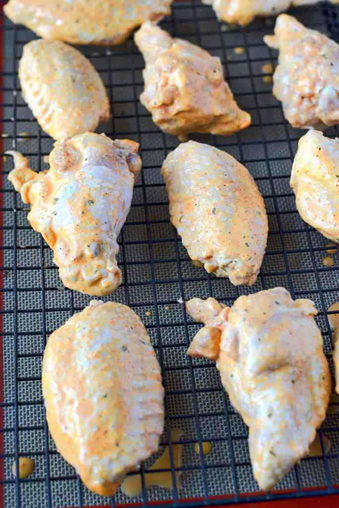 Spicy ranch chicken wings raw on a cooking rack