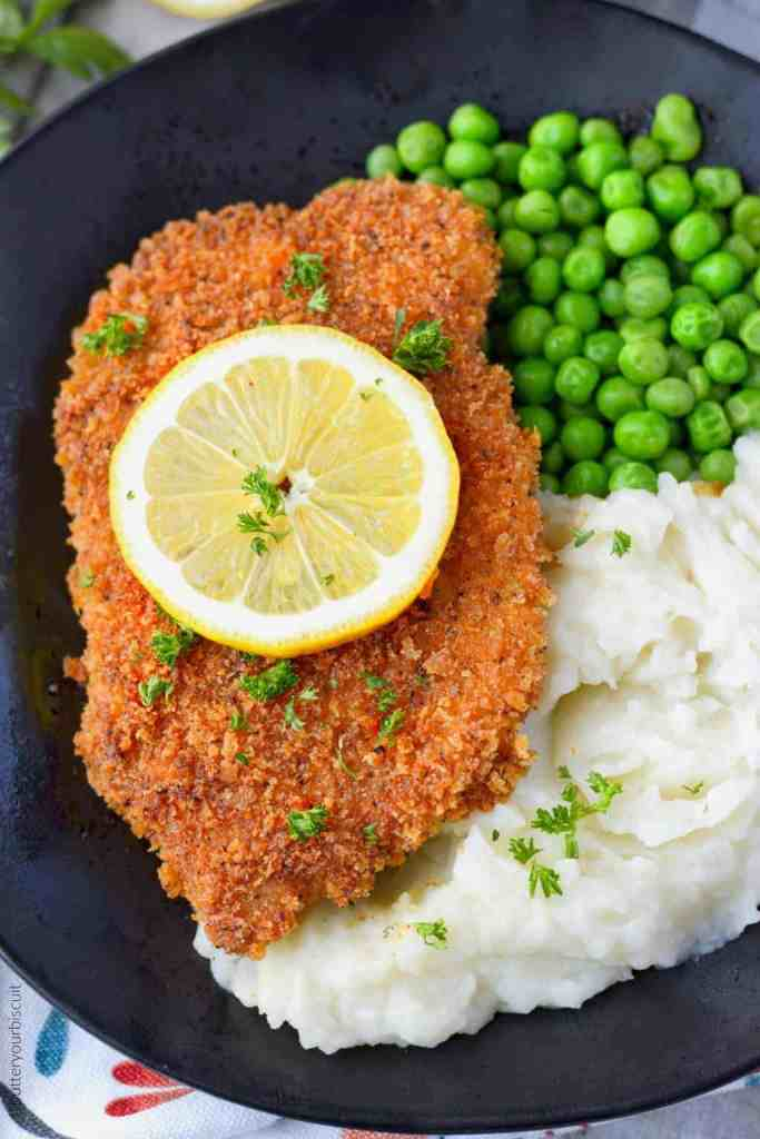 Pork schnitzel with mashed potatoes and green peas on a black plate