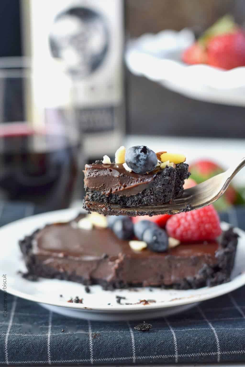 No bake chocolate mini tarts with strawberries, blueberries, rasberries and almond slivers on top on a white plate with a bite on a fork