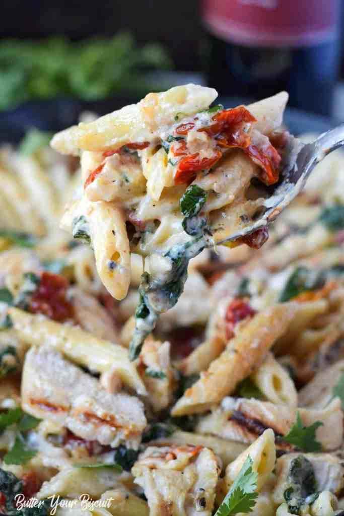 tuscan chicken pasta in a skillet with a serving spoon