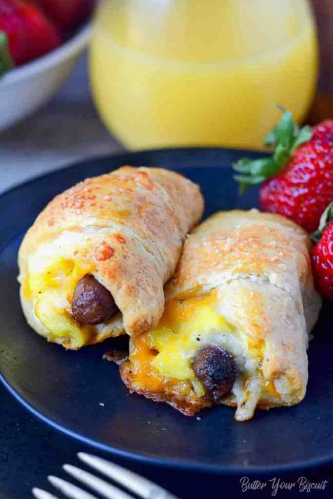 sausage egg cheese breakfast croissant roll up on a black plate with strawberries
