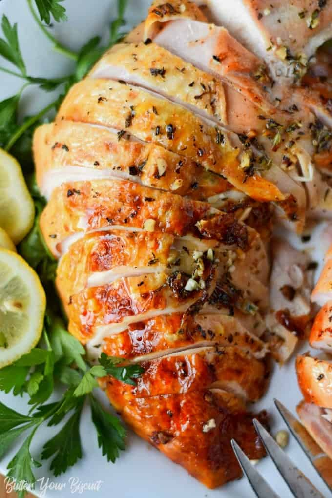 brined garlic herb turkey breasts sliced on a white platter