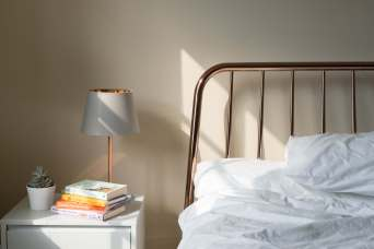 A rose gold metallic bedside table lamp