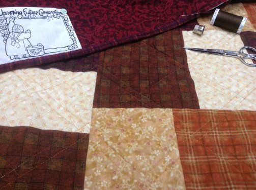 Sewing binding onto flannel quilt.