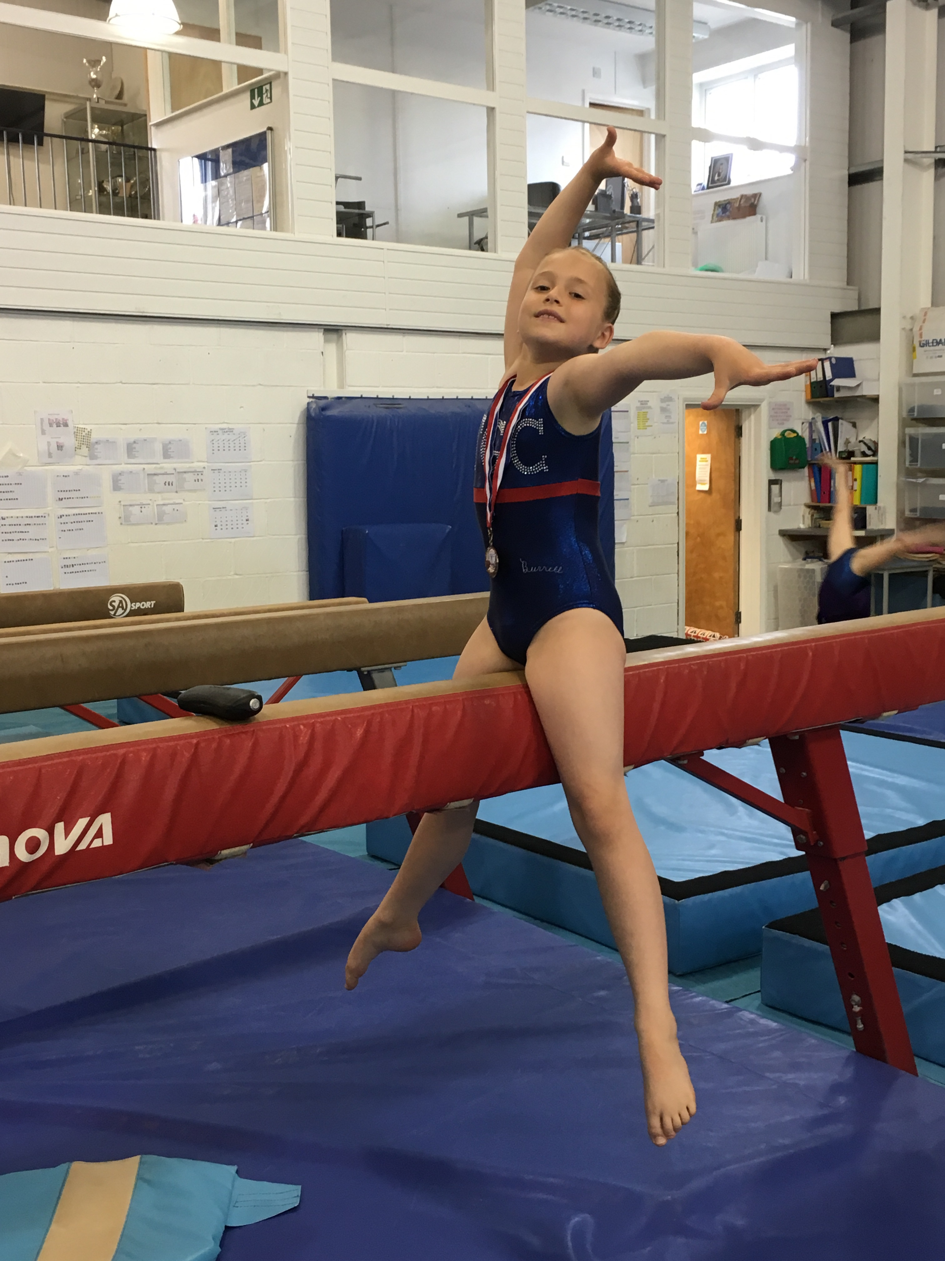 gymnast posing on beam with medal