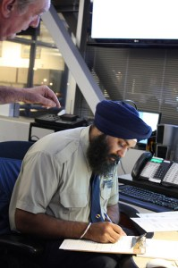 Still, in a room full of computers, there's a little paper work to be completed. Here long time transit employee, Barry, assists Kuldip, trainee (whose spelling and penmanship I checked).