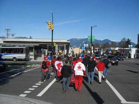 A crowd emerges from the curling venue and heads for King Edward Station on the Canada Line.