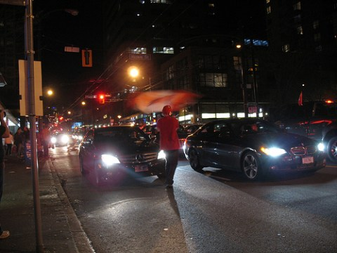 A fellow waving a flag in front of a car in the street.