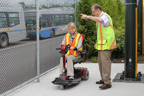 Julie from Access Transit tries getting on transit with a scooter at Vancouver Transit Centre, under the guidance of trainer Bert.