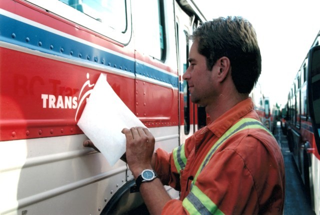 An employee installs the TransLink logo on the side of this bus after scraping off the BC Transit logo.