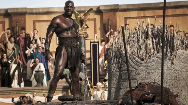 """The crowd cheers as Atticus (Adewele Akinnouye-Agbaje) defeats the """"Roman Soldiers"""" in the Amphitheatre in TriStar Pictures' POMPEII."""
