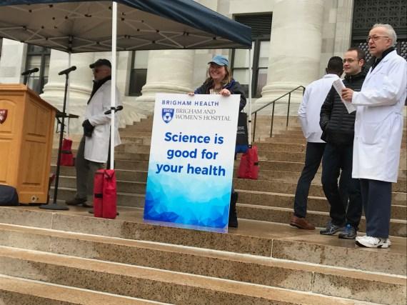 Jackie Slavik holds up a sign on behalf of Brigham Health