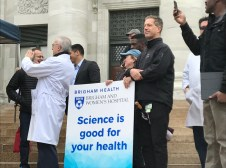 """Jackie Slavik and Paul Anderson hold up a sign declaring """"Science is good for your health"""""""