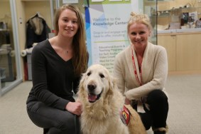 Two volunteers pose with golden tretriever during pet therapy event.