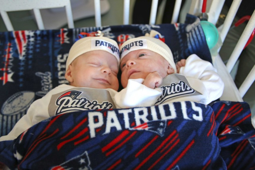 Benjamin and Samuel snuggle in their Patriots gear.