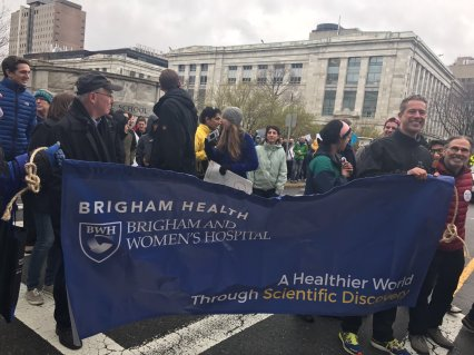 Paul Anderson (right) holds up the Brigham Health banner on the march from the HMS Quad