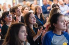 Audience members applaud speakers at the WBI Symposium.