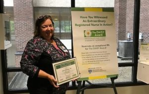 April Hughes poses with a DAISY award poster