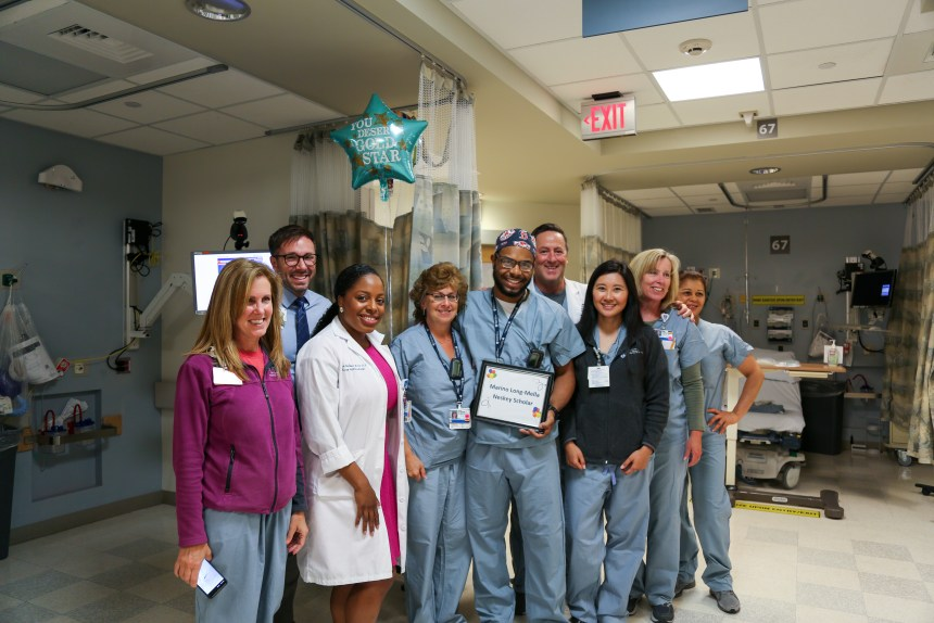 Nurse leaders and colleagues surprise Marino Long-Mella (center, holding certificate) with exciting news about his scholarship.