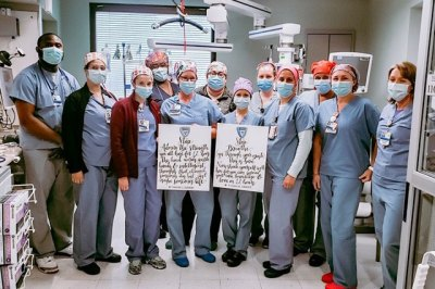 The Brigham Thoracic Surgery team holds up signs