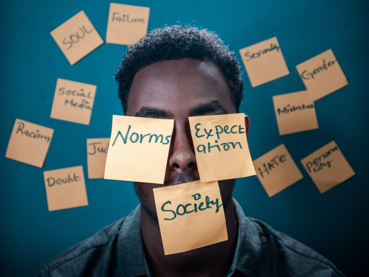 Male person of colour with post its on face and wall including words such as 'norms', 'society' and 'expectations