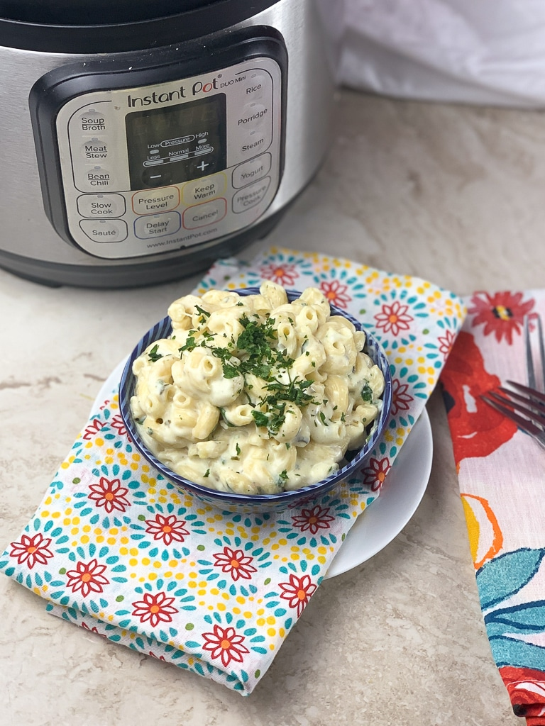 macaroni and cheese side view topped with parsley with instant pot in the back