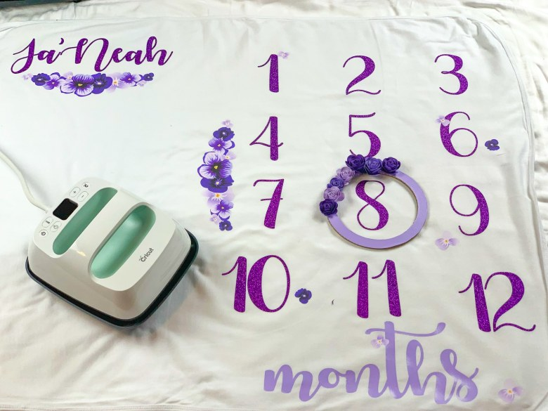 cricut easypress 2 ontop of a baby milestone blanket with lavender and purple letters