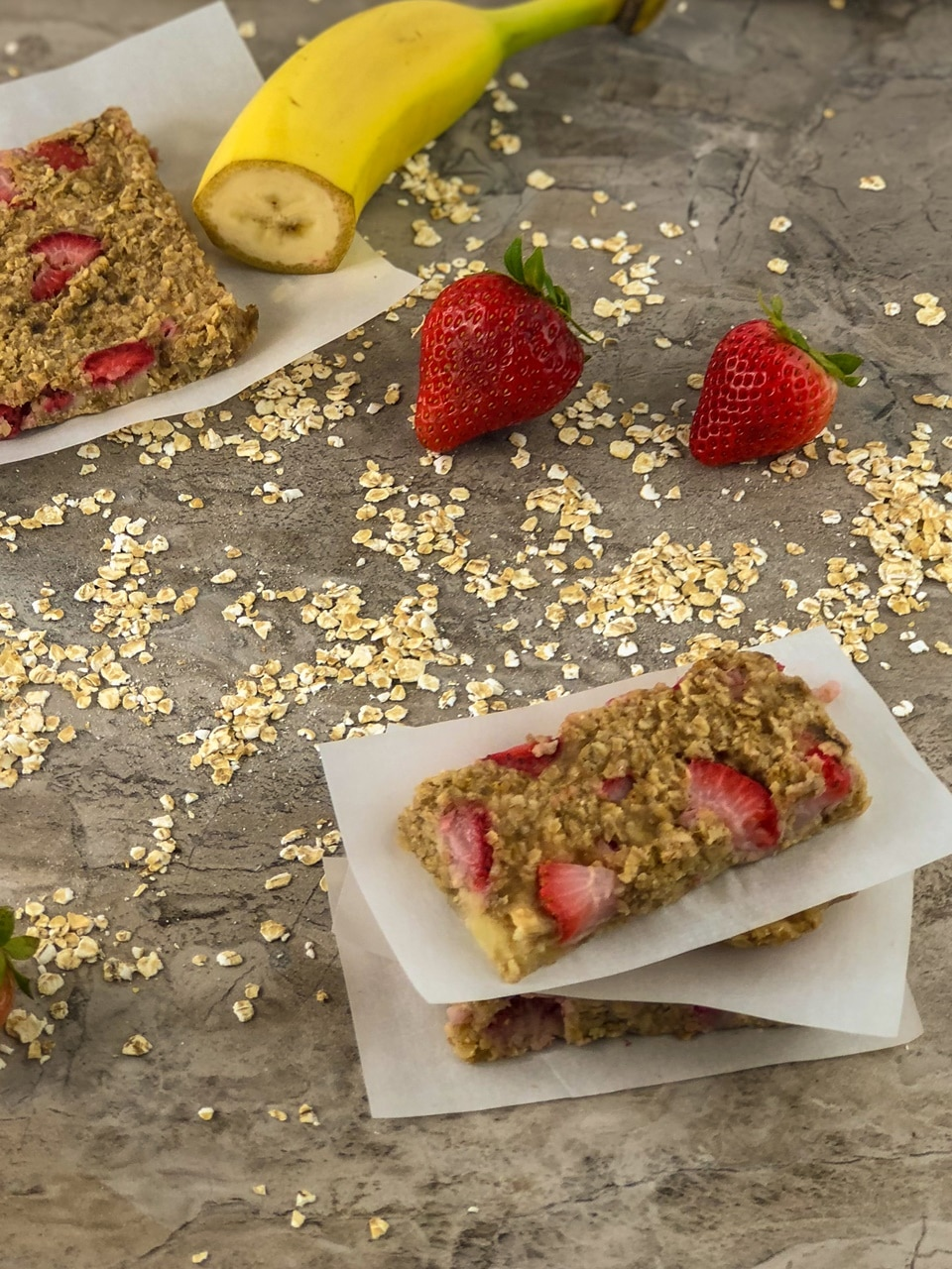 Image of Oatmeal Strawberry bars with a bannana in the background and oatmeal on the table.