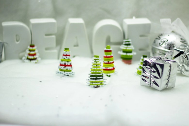 white background with the words peace and red green and white christmas tree ornaments