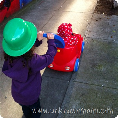 Little-girl-pushing-another-little-girl-in-a-toy-car