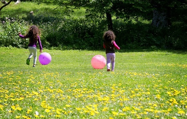 Two little girls playing ball in the park