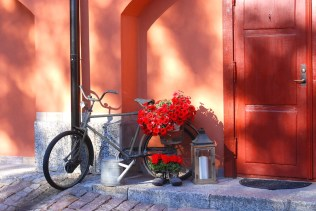 Bicycle with red flowers in back basket resting against the deep adobe-colored wall of an apartment at the Kastellet Bed & Breakfast. By C.S. White