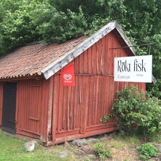 "This rustic red wooden shed advertises ""Rokt Fisk"" marks the quaint lunch stop known for its fresh smoked fish menu items, Toro, Stockholm, Sweden. By C.S. White"