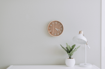 a clean and white console with a clock, lamp and plant.