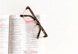 a pair of glasses and an open bible with highlighted bible verses about infertility