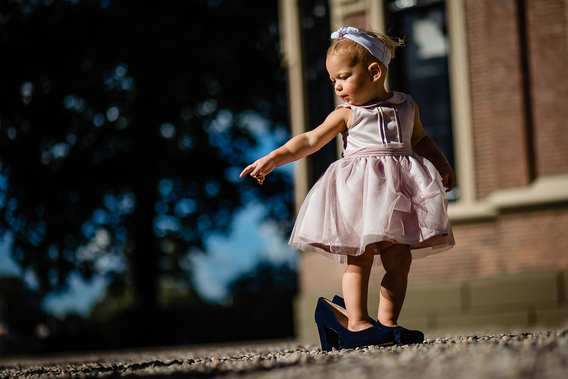 foto van een klein meisje dat de schoenen van haar moeder ingepikt heeft